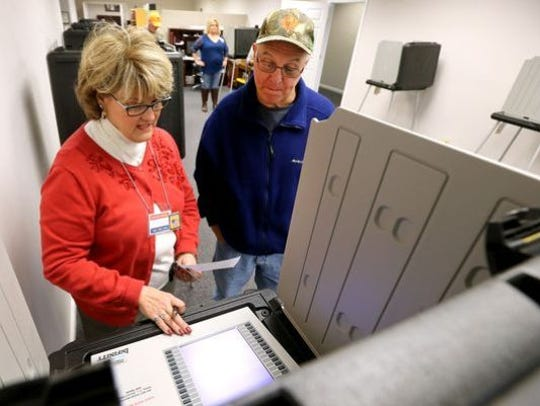 Poll worker Beth Wright shows Alan Leyo how to use