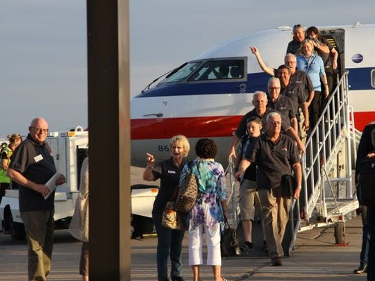 Passengers, including local elected officials, step off of the plane that marked the first American Airlines flight from Phoenix to Roswell.