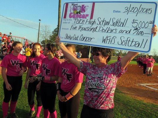 Tate softball coach Melinda Wyatt hoists up a donation from West Florida High softball during last year's Strike Out Cancer game.