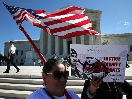 Immigration advocates protest in front of the Supreme