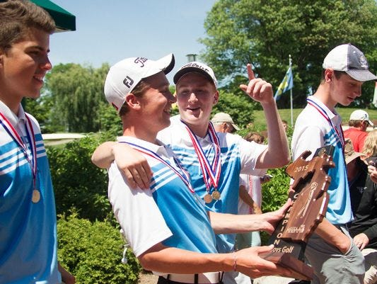 Owen Rush (middle right) and the Lansing Catholic golfers celebrate their Division 3 state championship victory last season. Rush has a chance to be a part of four championship teams this season.