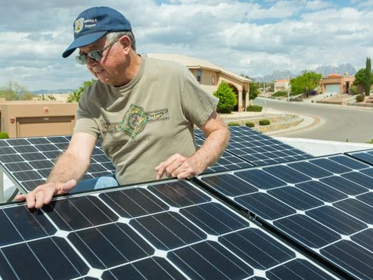 Bill Newton, of Las Cruces, looks over his solar panel on the roof of his home on Monday, April 18, 2016.