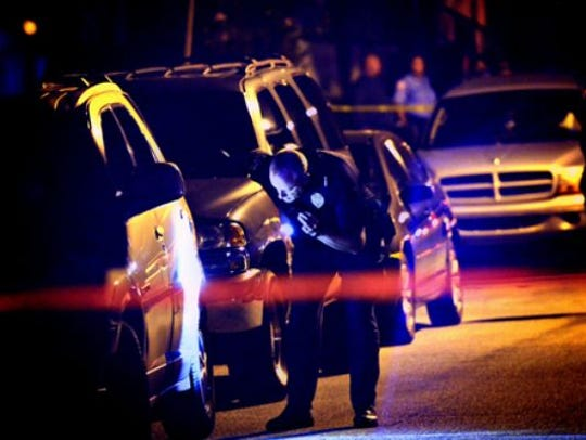 York City police officers search for evidence after