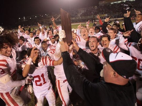 The Palm Springs Indians hold up the 2014 CIF championship trophy.