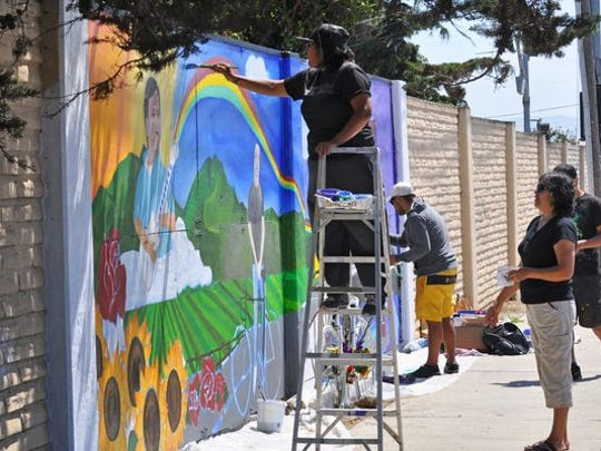 Miembros del colectivo de artistas Tunas de Nopal (Prickly Pear) trabajan en el mural en honor a Adrián Garcia.