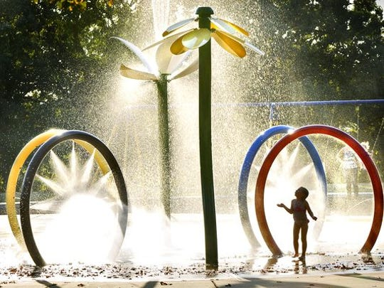 A young girl revels in the spray from the splash pad