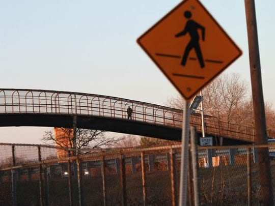 A passenger uses the pedestrian bridge over Interstate
