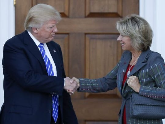 Donald Trump and Betsy DeVos shake hands after her
