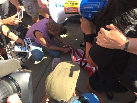 Protesters attempt to burn a flag outside Quicken Loans