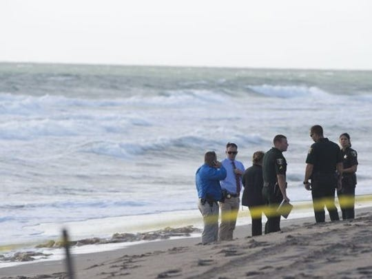 A group from the Martin County Sheriff's Office preside over a body that washed up from the ocean April 11 south of the House of Refuge in Stuart. A boat capsized shortly after departing from Sansprit Park in Port Salerno, claiming the lives of two adults and one child.