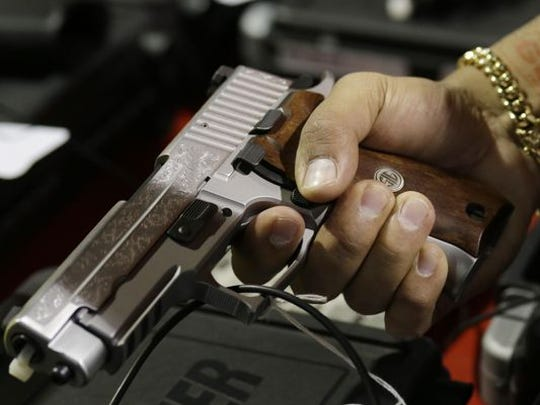 A customer looks at a SIG Sauer hand gun at a gun show held by Florida Gun Shows, Saturday, Jan. 9, 2016, in Miami. President Barack Obama announced proposals this week to tighten firearms sales through executive action.