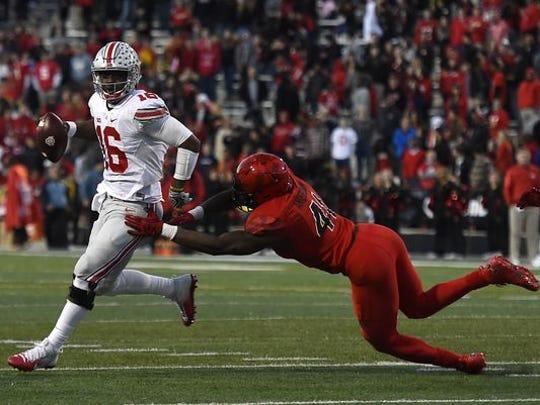 J.T. Barrett of Ohio State runs past a Maryland defender.