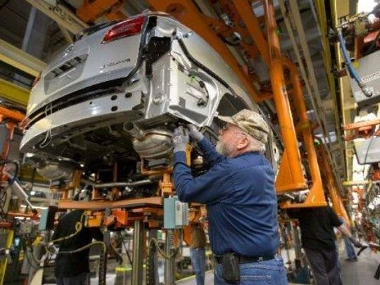 An auto worker helps assemble a Buick Enclave at the Lansing Delta Township Assembly plant in April 2016.
