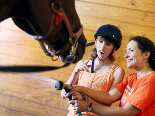Volunteer Jen Frey of Dover, right, helps Christina Wildasin spray down horse Sam after a lesson in 2015 at Leg Up Farm in Mount Wolf.