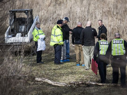 Investigators at the scene of a Feb. 14 slaying. A