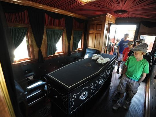 Youths in Ashland, Ohio, file through the somber interior of the replicated Lincoln funeral coach with its black drapery, polished woodwork and black muslin coffin.