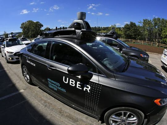A group of self driving Uber vehicles position themselves