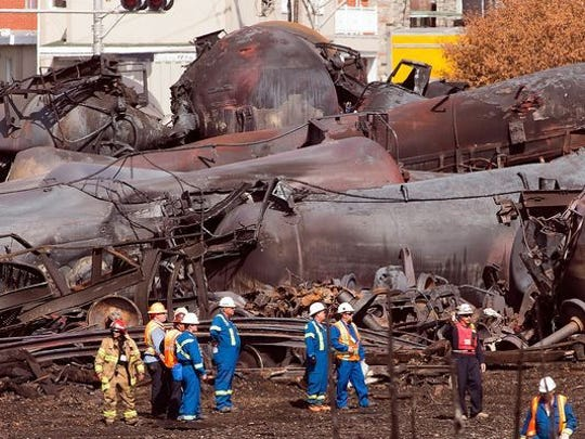 Workers stand before mangled tanker cars Tuesday, July 16, 2013, at the crash site of the train derailment and fire in Lac-Megantic, Quebec. The July 6, 2013, accident left 37 people confirmed dead and another 13 missing and presumed dead.