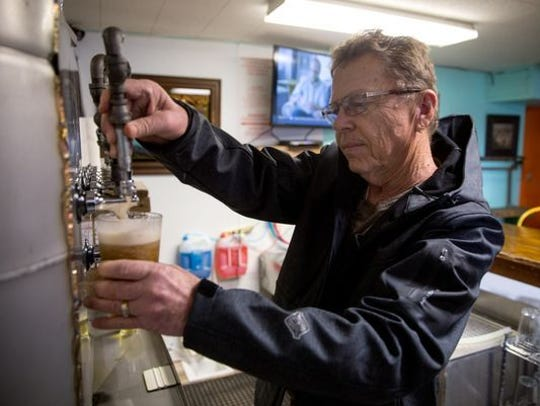A bartender pours a nice cold draft beer.