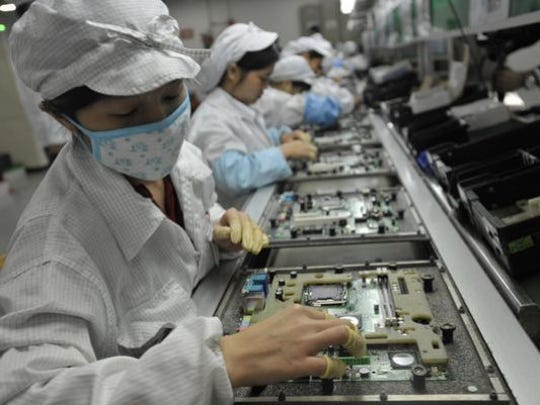 Workers assemble electronic products at a Foxconnn factory in Shenzhen, China, in 2010.