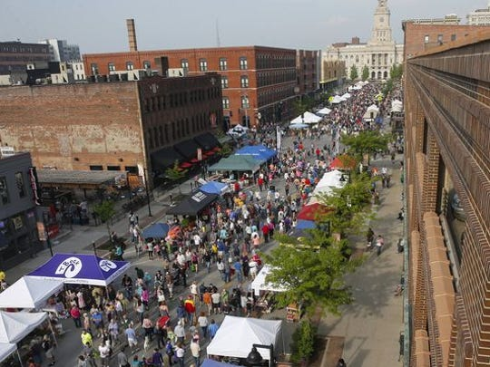 Shoppers walk along Court Avenue in Des Moines gathering fresh produce, sweet treats and other items during the opening day of the 2016 downtown farmers market.