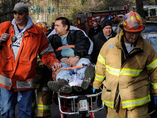 Metro North Railroad engineer William Rockefeller is wheeled on a stretcher Dec. 1, 2013, after the commuter train he was driving derailed in the Bronx.