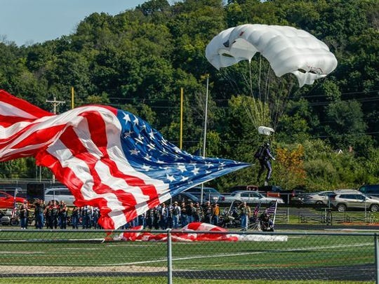 A parachutist lands on the Lakota West football field in West Chester during the funeral service for Army Master Sgt. Corey Hood. Hood, 32, a Lakota West graduate and member of the Army's Golden Knights parachute team, died Aug. 16, 2015, following a performance at the Chicago Air and Water Show.