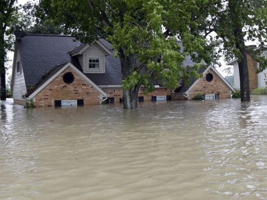 A home is surrounded by floodwaters from Tropical Storm Harvey on Aug. 28, 2017, in Spring, Texas.  Also in Spring, Dover-native Melissa VanOrman is waiting for the waters to recede from around her apartment building.