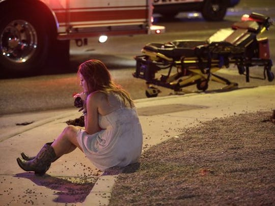 A woman sits on a curb at the scene of a shooting outside of a music festival along the Las Vegas Strip in Las Vegas. Multiple victims were being transported to hospitals after a shooting late Sunday at a music festival on the Las Vegas Strip.