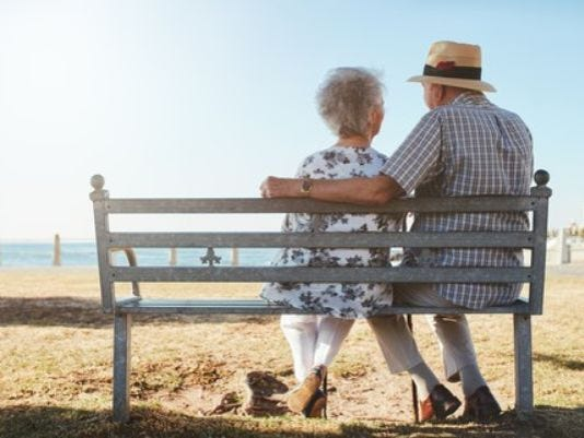 636489698679531805-elderly-senior-couple-sitting-on-a-bench-on-the-beach-large.jpg