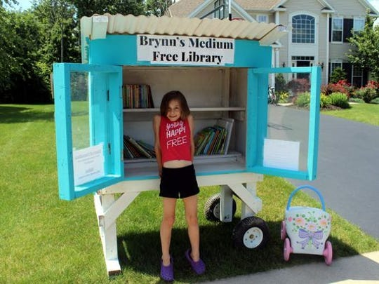 Six-year-old Brynn Anderson with her medium free library outside her Penfield home.