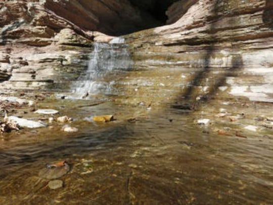 Water flows out of the mouth of Cobb Cave along the