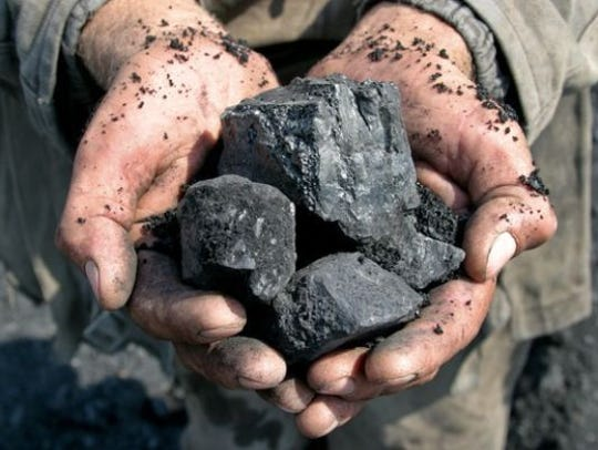 A coal miner holds chunks of coal in this undated file