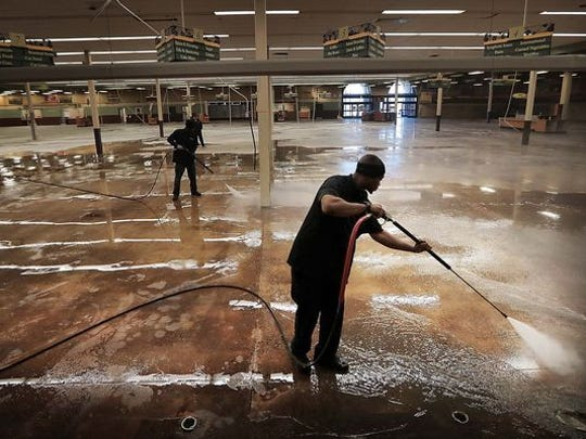 Kenny Johnson of ServePro pressure washes the floor of the old Kroger in December as work began on the property to clear the way for new tenants.