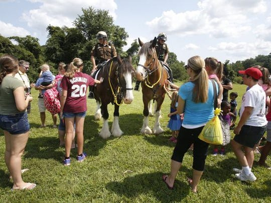 New Castle County Police Mounted Patrol officers Erich Selhorst (left) on Commander and Maura Schultz on Big Red draw a crowd during New Castle County Family Fun Day at Carousel Park.
