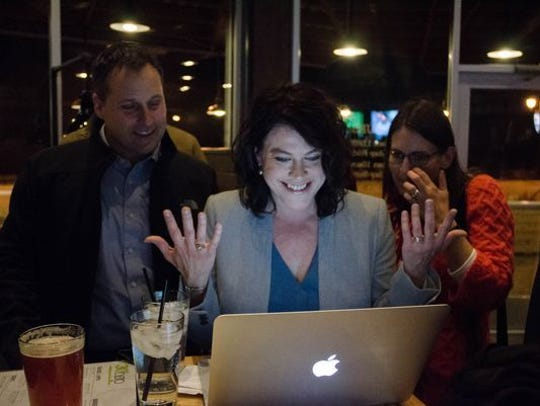Meghann Foster, center, reacts as she realizes she