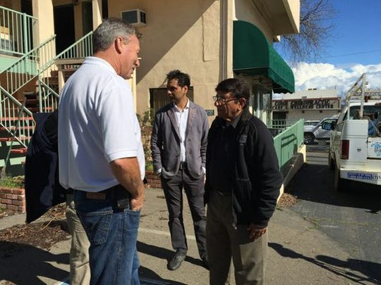 Vijay Soni, right, talks to Alex Gabel of Gabel's Hauling & Demolition, left, last February after a press conference to announce the sale of the Redding Inn. Soni was representing the new owners.