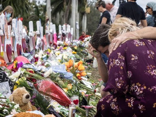 People visit a makeshift memorial in front of the Marjory Stoneman Douglas High School in, Parkland, Florida on Feb. 20, 2018.