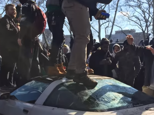 A Philadelphia man is accused of being among spectators who watched the Super Bowl parade from atop a parked car.