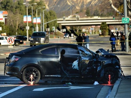 A crashed Toyota Scion sits in the intersection of