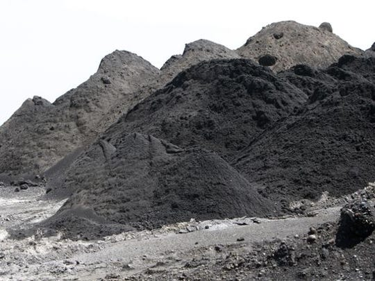 Gritty coal ash, left over when coal is burned, is collected in a landfill at the John Twitty Energy Center. The ash solidifies after contact with water and is covered in topsoil and seeded with grass once it reaches the proper elevation.