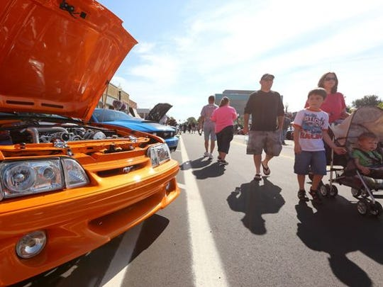 Families look at Mustangs at the Ford Mustang Alley display during the 2015 Woodward Dream Cruise on Saturday, August 15, 2015.