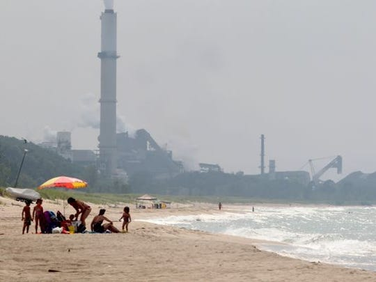 People enjoy the beach on the Indiana shore of Lake Michigan, east of ArcelorMittal's Burns Harbor steel mill.