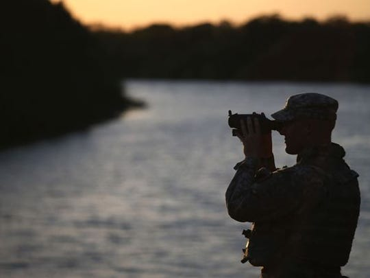 A Texas National Guard soldier scans the Mexican side of the U.S.-Mexico border on September 11, 2014 in Havana, Texas.