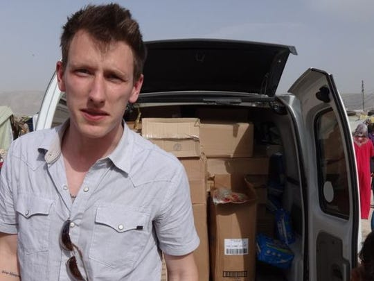 This undated file photo provided by the Kassig Family shows Peter Kassig standing in front of a truck filled with supplies for Syrian refugees. A new graphic video purportedly produced by Islamic State militants in Syria released Sunday Nov. 16, 2014 claims U.S. aid worker Kassig was beheaded.