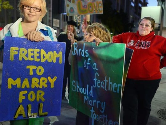 Sam Aaquist, 14, her brother, Billy, 10 and their mom, Joy, right, during the Celebration Rally for Marriage Equality at the Downtown Plaza Tuesday evening Oct. 7, 2014.