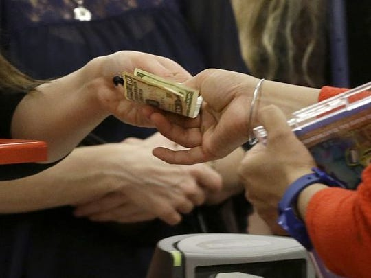 A woman pays with cash while shopping at a Target in California during last year's holiday shopping season.