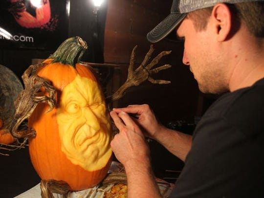 Mike Brown puts the finishing touches on a pumpkin.