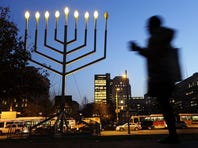 A man passes a large menorah in Philadelphia, PA