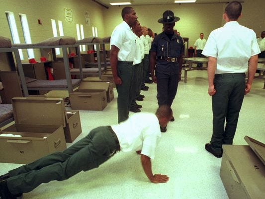 A Sussex Correction's boot camp cadet gives drill instructor Spencer Brittingham some push-ups during a house inspection in 1997.
